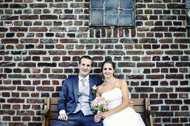 Hochzeitsfotografie Brautstrauß Blumen Hände Paar Braut Bräutigam Mauer Wand Klinker